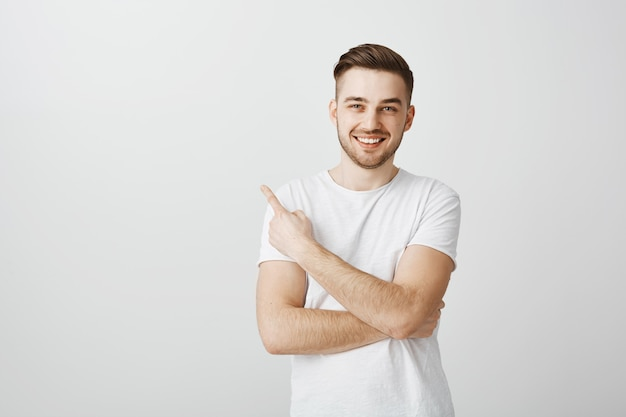 Pleased handsome young man in white t-shirt pointing finger upper left corner