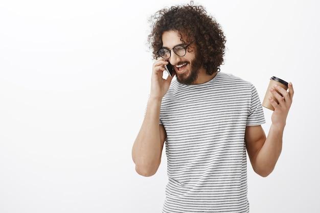 Felice ragazzo adulto felice con i capelli ricci, con gli occhiali e t-shirt a righe alla moda, tenendo la tazza e gesticolando mentre parla sullo smartphone