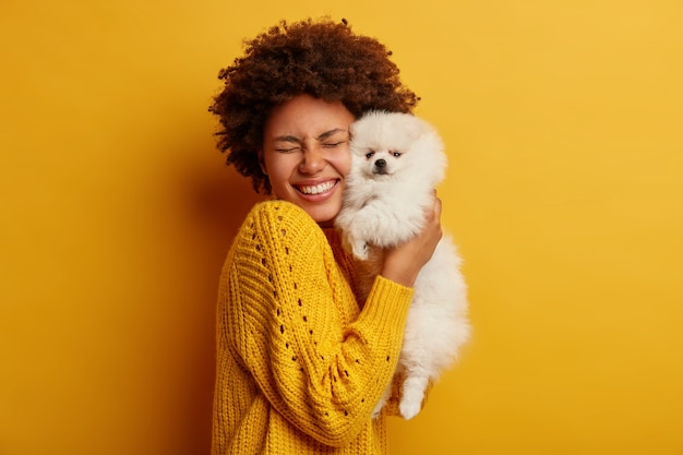 Pleased happy afro girl gets lovely puppy, plays and embraces four legged friend with love, stands against yellow background