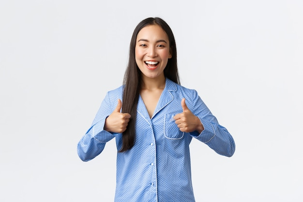 파란 잠옷을 입은 행복한 아시아 소녀는 놀라운 제품, 프로모션 추천, 좋은 결과에 기뻐하며 잘 놀았다거나 잘했다고 말합니다