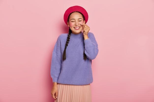 Довольная счастливая азиатская женщина лепит маленькое сердечко руками, делает корейский знак, носит красный берет, повседневный джемпер и юбку, приятно улыбается, находится в хорошем настроении, изолирована от розовой стены