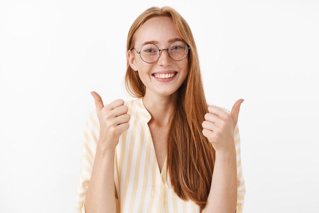 Soddisfatta, felice ed entusiasta, rossa creativa rossa femminile con graziose lentiggini in bicchieri e camicetta a strisce gialle, alzando i pollici in segno di approvazione e concorda gesto sorridente felice Foto Gratuite