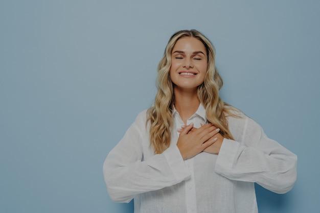 Довольная счастливая благодарная женщина со светлыми волнистыми волосами в белой негабаритной рубашке, показывающая признательность, любовь и благодарность, взявшись за руки на груди, с закрытыми глазами, изолированными на синей стене
