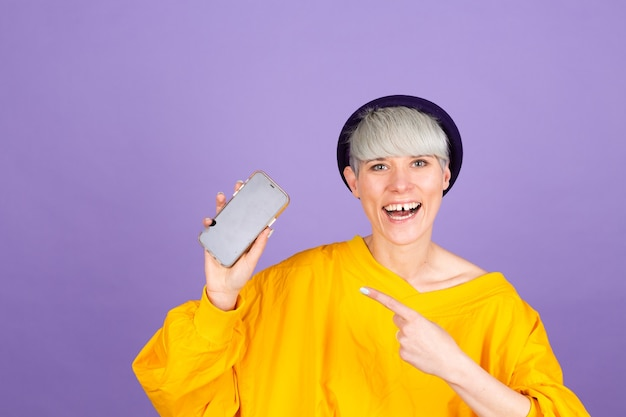 Pleased happy woman points with index finger at blank screen, showing modern device