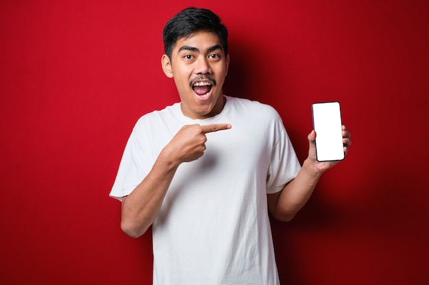 赤い背景の上に携帯電話の画面を指しているスマートフォンを保持しながらカメラに微笑んで白いtシャツの幸せな若いアジア人の男