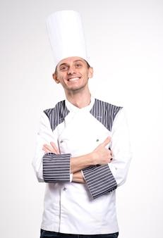 Довольный счастливый молодой шеф-повар позирует на белом фоне стены в униформе.