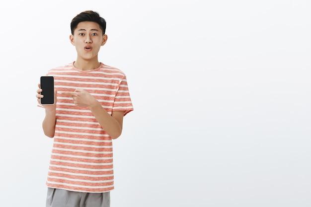 Довольный счастливый молодой симпатичный азиатский парень в полосатой футболке, стоящий слева от копировального пространства, держа смартфон, указывая на экран мобильного телефона, показывая удивительный новый телефон друзьям в восторге