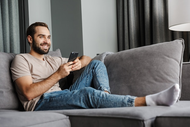 A pleased happy young man indoors at home on sofa using mobile phone.