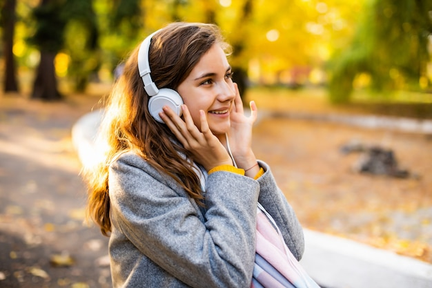 Pleased happy young teenage girl student sitting outdoors in beautiful autumn park listening music with headphones.