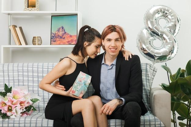 행복한 여성의 날에 거실에서 소파에 앉아 있는 선물을 들고 젊은 부부를 기쁘게 껴안았습니다. 무료 사진