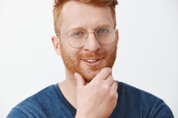 青いtシャツとメガネで興味をそそられる創造的でハンサムな赤毛のボスを喜ばせ、あごひげに触れ、満足した気持ちから笑って、不思議そうに見えます