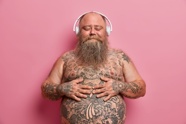 Pleased joyful bearded adult man keeps hands on big belly, enjoys awesome music in good quality wireless headphones, has problem of overweight, closes eyes and imagines something very pleasant