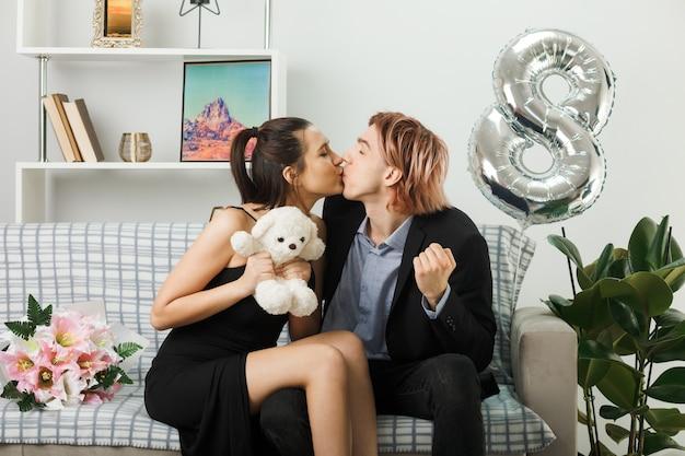 Piacere di baciarsi una giovane coppia durante la felice giornata della donna con l'orsacchiotto seduto sul divano nel soggiorno