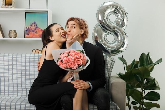 Довольно целовать друг друга молодая пара в счастливый женский день девушка держит букет, сидя на диване в гостиной
