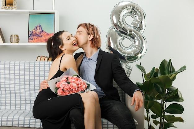 リビングルームのソファに座っている花束と幸せな女性の日に若いカップルにお互いにキスを喜んで