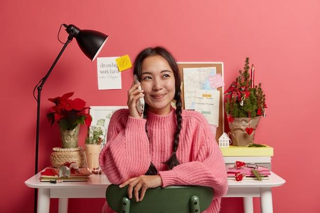 喜んでいる韓国の女の子はスマートフォンで良いニュースを聞いて、目をそらし、カジュアルな服を着て、自分の家のキャビネットでポーズをとり、セッションの準備をし、テーブルの上に小さな飾られたクリスマスツリー
