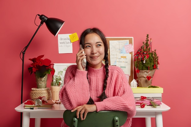 Pleased korean girl listens good news on smartphone, looks away, dressed casually, poses in own home cabinet, prepares for session, small decorated christmas tree on table