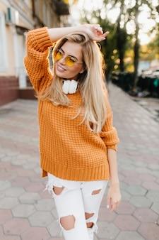 通りでポーズをとっている間、ふざけて笑顔で目をそらしている破れたズボンの満足している女性