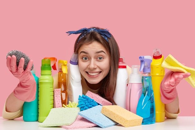 Pleased lady with european appearance, toothy smile wears headband, looks positively through detergents