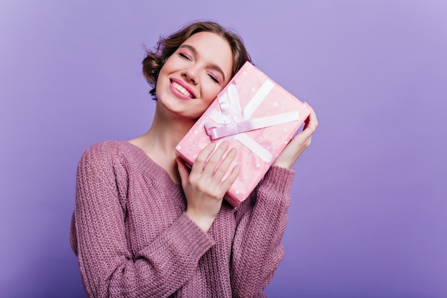 Pleased lady with glamorous makeup posing with new year gift on purple wall. dreamy short-haired girl standing with eyes closed , holding birthday present.