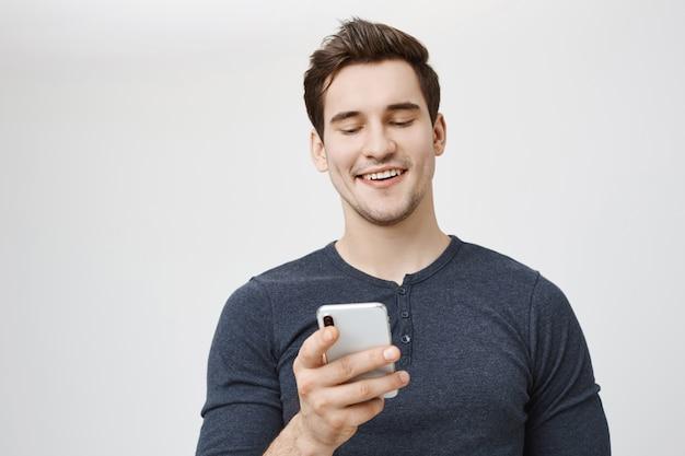 Довольный смеющийся человек смотрит на экран мобильного телефона и улыбается