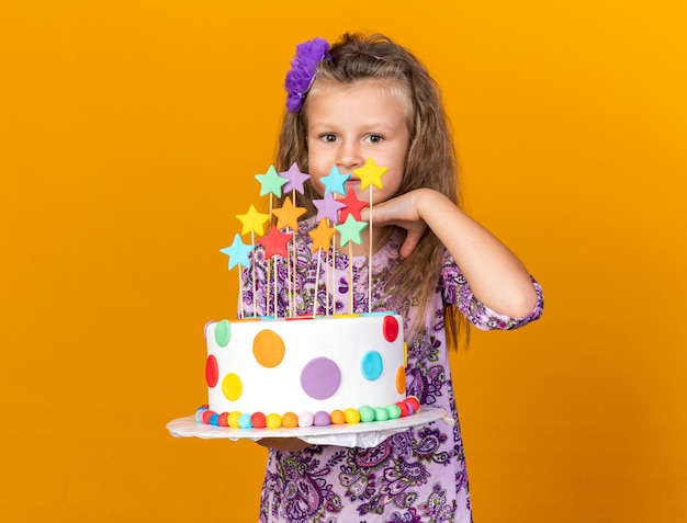 Pleased little blonde girl holding birthday cake and putting hand on chin isolated on orange wall with copy space