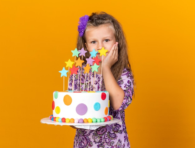 Compiaciuta bimba bionda con la torta di compleanno e mettendo la mano sul viso isolato sulla parete arancione con spazio copia