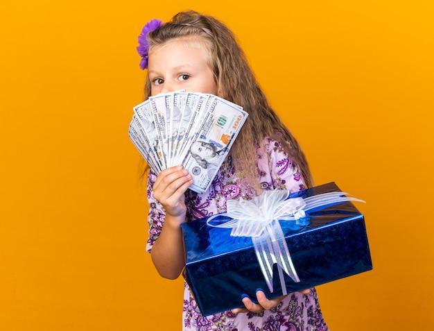 Довольная маленькая блондинка держит подарочную коробку и деньги перед ее лицом, изолированным на оранжевой стене с копией пространства
