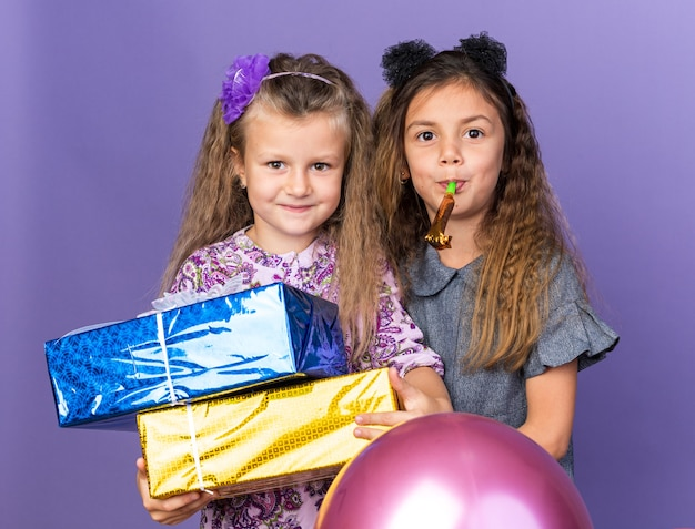 Pleased little blonde girl holding gift boxes and standing with little brunette girl blowing party whistles and holding helium balloons isolated on purple wall with copy space