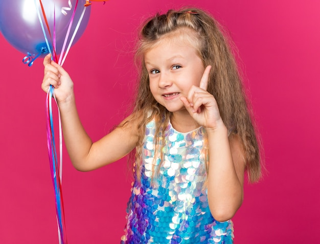 Pleased little blonde girl holding helium balloons and pointing up isolated on pink wall with copy space