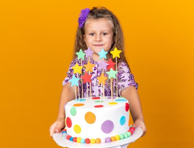 Compiaciuta bimba bionda che tiene e guarda la torta di compleanno isolata sulla parete arancione con spazio copia