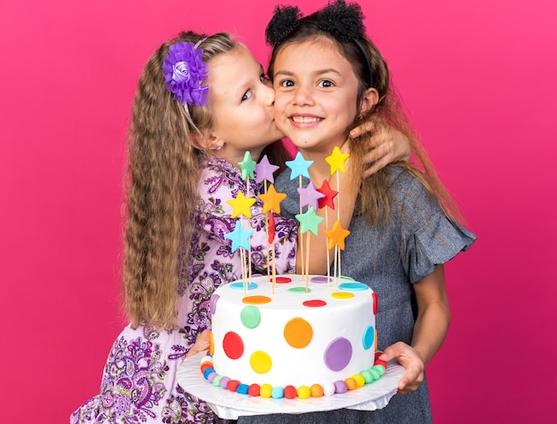Pleased little blonde girl kissing smiling little caucasian girl holding birthday cake isolated on pink wall with copy space