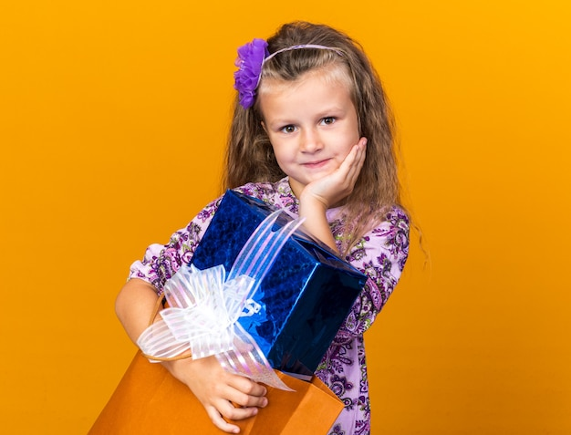 Pleased little blonde girl putting hand on face and holding gift box isolated on orange wall with copy space
