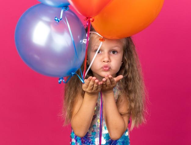 Compiaciuta bambina bionda che manda un bacio con le mani che tengono palloncini di elio isolati sulla parete rosa con spazio di copia
