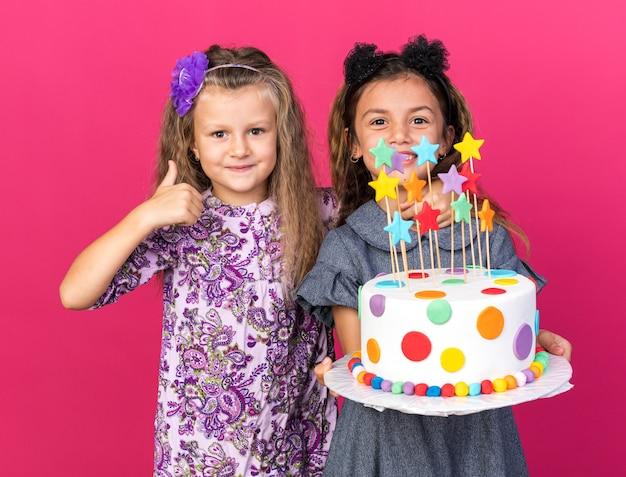 Довольная маленькая блондинка показывает палец вверх, стоя с улыбающейся маленькой кавказской девушкой, держащей торт ко дню рождения, изолированную на розовой стене с копией пространства