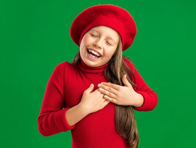 コピースペースで緑の壁に隔離された目を閉じて心に手を保つ赤いベレー帽を身に着けている幸せな小さなブロンドの女の子