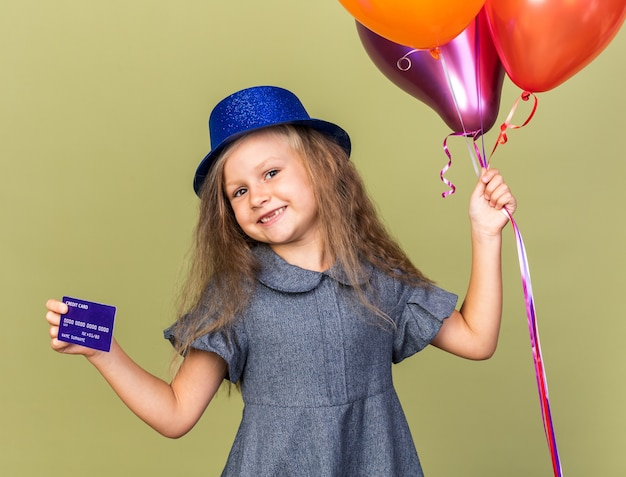 Pleased little blonde girl with blue party hat holding helium balloons and credit card isolated on olive green wall with copy space