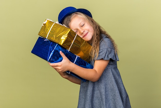 Pleased little blonde girl with blue party hat holding and putting head on gift boxes isolated on olive green wall with copy space