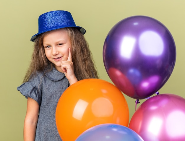 Pleased little blonde girl with blue party hat putting hand on chin and standing with helium balloons isolated on olive green wall with copy space