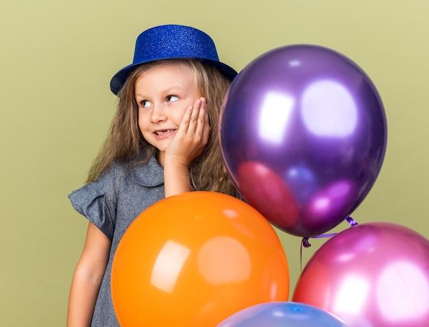 Compiaciuta bambina bionda con cappello da festa blu in piedi con palloncini di elio mettendo la mano sul viso e guardando il lato isolato sulla parete verde oliva con spazio di copia