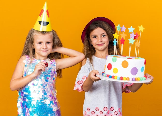 Pleased little blonde girl with party cap holding whistle and standing with little caucasian girl wearing purple hat and holding birthday cake isolated on orange wall with copy space