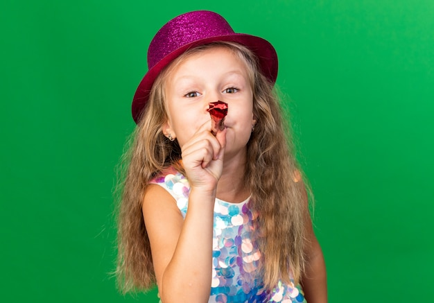 Pleased little blonde girl with purple party hat blowing party whistle isolated on green wall with copy space