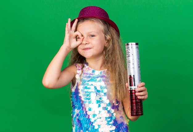 Pleased little blonde girl with purple party hat holding confetti cannon and looking  through fingers isolated on green wall with copy space Free Photo