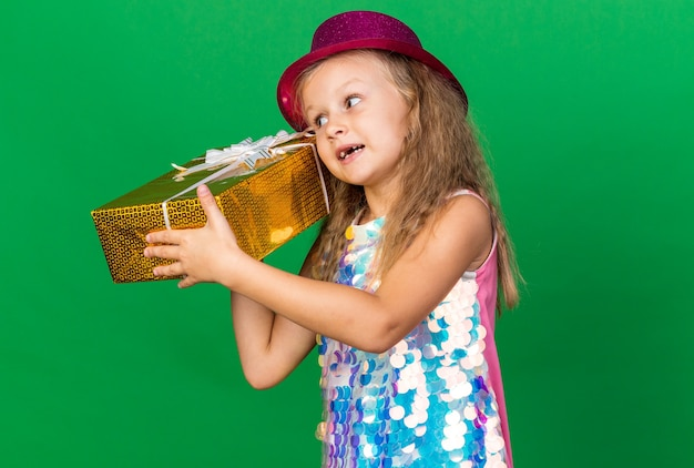 Pleased little blonde girl with purple party hat holding gift box close to her ear isolated on green wall with copy space