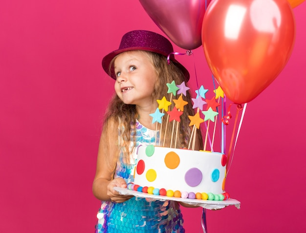Pleased little blonde girl with purple party hat holding helium balloons and birthday cake isolated on pink wall with copy space