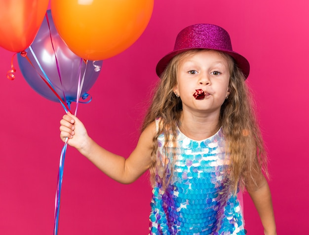 Pleased little blonde girl with purple party hat holding helium balloons and blowing party whistle isolated on pink wall with copy space