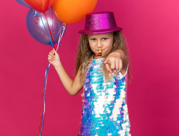 Pleased little blonde girl with purple party hat holding helium balloons and blowing party whistle pointing  isolated on pink wall with copy space