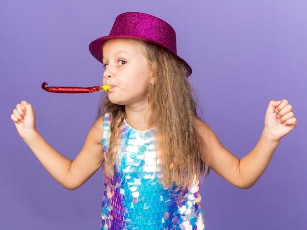 Lieta bambina bionda con cappello da festa viola che soffia fischietto di festa e tenendo i pugni isolati sulla parete viola con spazio di copia