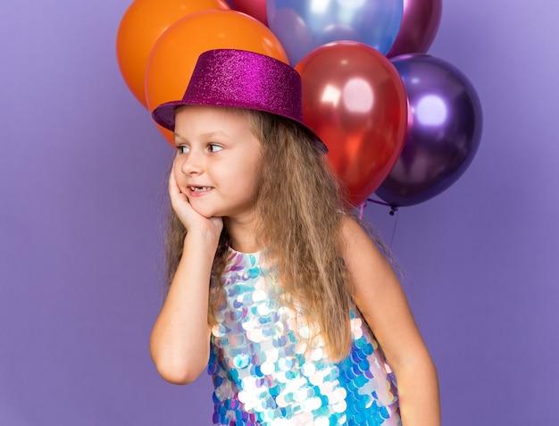 Compiaciuta bambina bionda con cappello da festa viola che si mette la mano sul viso e guarda il lato in piedi con palloncini di elio isolati sulla parete viola con spazio di copia