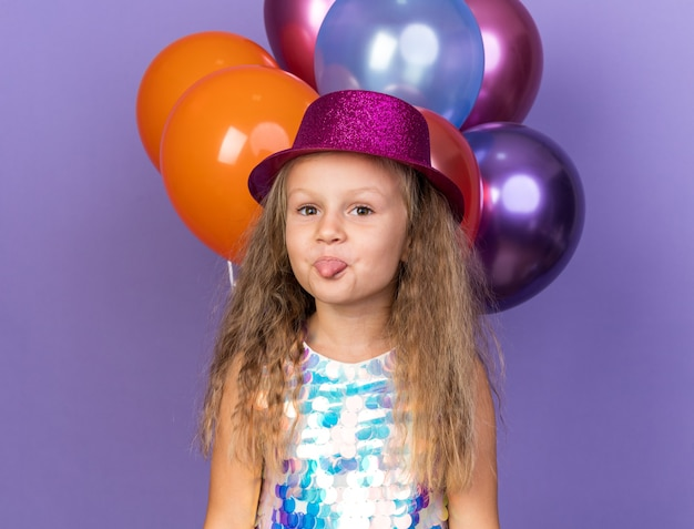 Pleased little blonde girl with violet party hat stucks out tongue standing with helium balloons isolated on purple wall with copy space